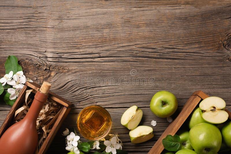 Reife grüne Äpfel in der Holzkiste mit Niederlassung von weißen Blumen, von Glas und von Flasche Apfelwein auf einem Holztisch lizenzfreie stockbilder