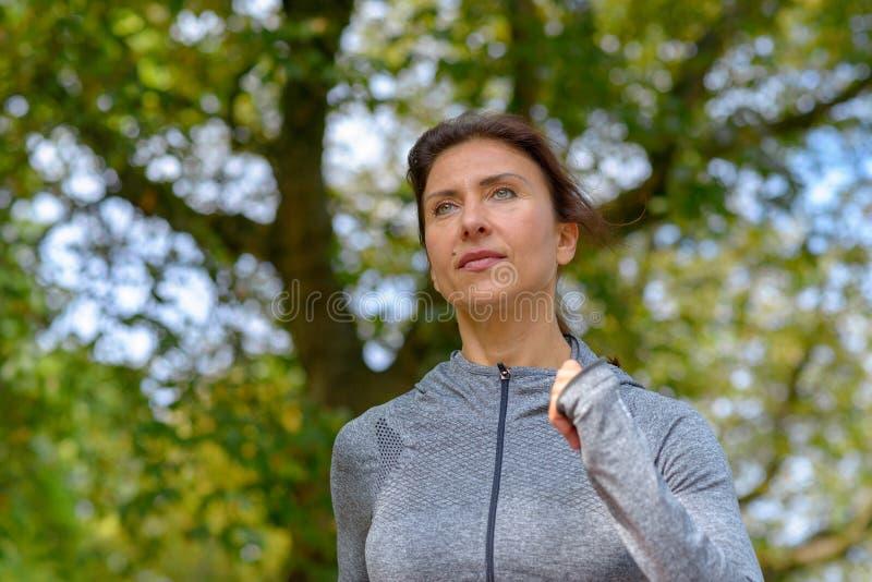 Reife graue Jacke tragende und rüttelnde Frau lizenzfreies stockbild
