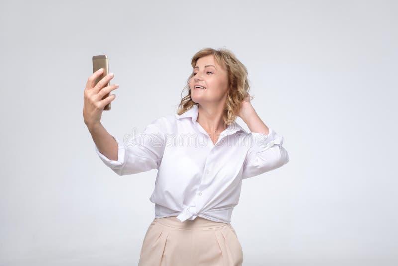 Reife hübsche Frau in der formellen Kleidung, die selfie an ihrem Telefon macht stockfotos