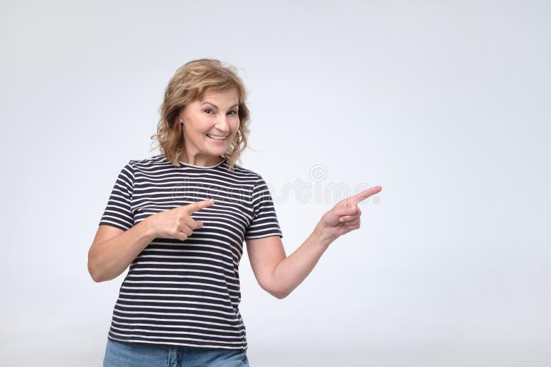 Reife hübsche Frau, die Finger zeigt, um oben in Verlegenheit zu bringen, Konzept des Anzeigenproduktes lizenzfreies stockbild