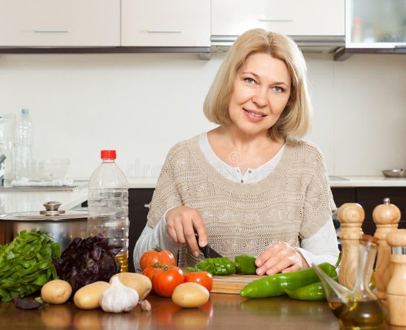 Reife Hausfrau, die das Mittagessen kocht stockfotos