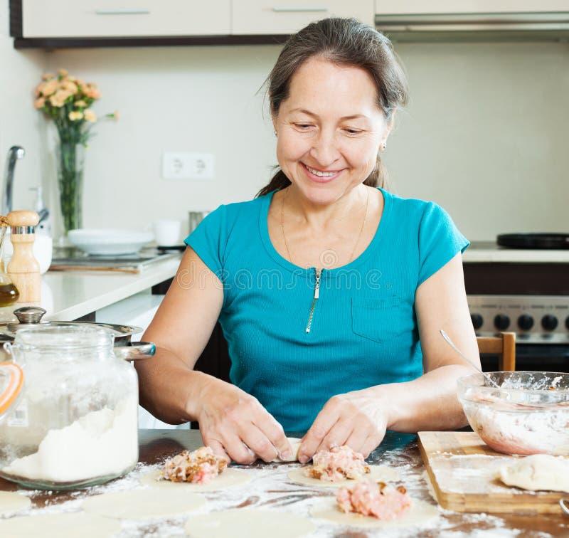 Reife Hausfrau, die Fleischmehlklöße macht stockbild