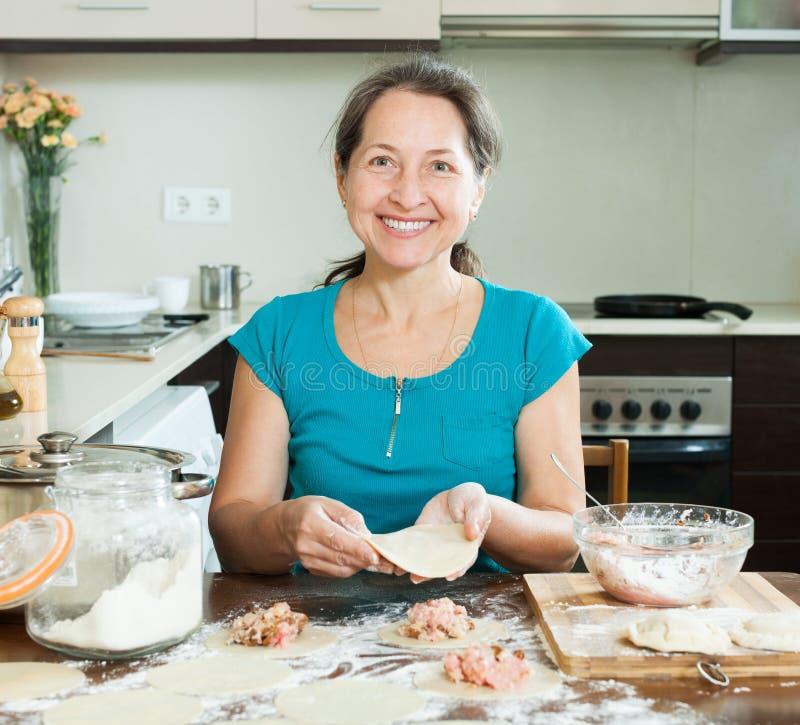Reife Hausfrau, die Fleischmehlklöße macht stockfotografie