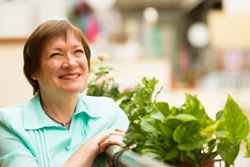 Reife Hausfrau, die schönes Wetter auf Terrasse genießt stockfotos