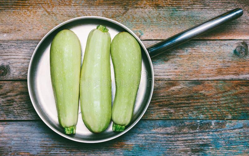 Reife hellgrüne Zucchini drei mit Wanne auf hölzernem Retro- Hintergrund, Draufsicht stockbild