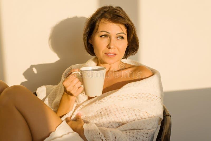 Reife lächelnde Frau, die zu Hause im Stuhl in der woolen gestrickten Decke mit Schale des heißen Getränks, Herbstwinterart sitzt stockfotos