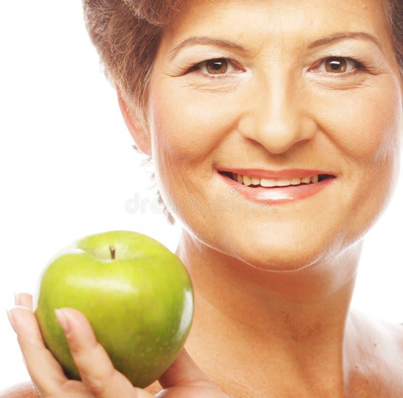 Reife lächelnde Frau mit grünem Apfel stockfotos