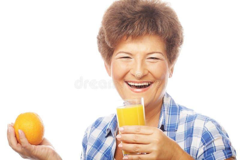 Reife lächelnde Frau mit Orangensaft stockfotografie