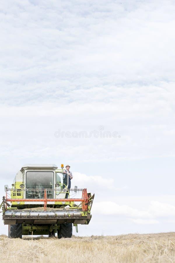 Reife Landwirtstellung auf Erntemaschine am Feld gegen Himmel lizenzfreies stockbild