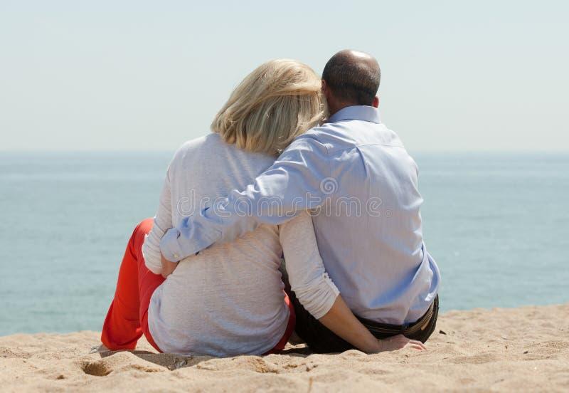 Reife Liebhaber, die auf Strand sitzen stockbilder