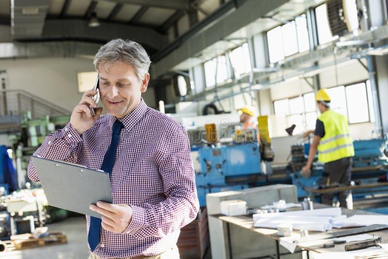 Reife männliche Aufsichtskraft, die Klemmbrett bei der Unterhaltung am Handy in der Industrie betrachtet stockbild
