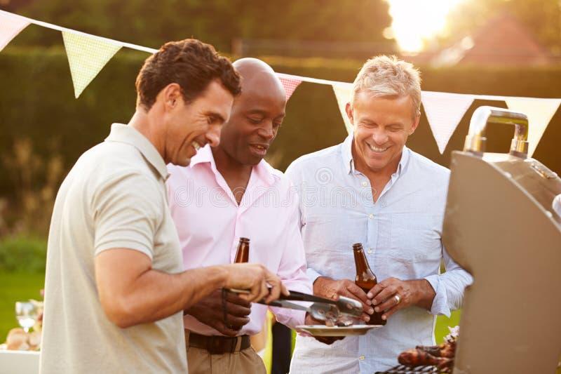 Reife männliche Freunde, die Sommer-Grill im Freien genießen stockfotografie