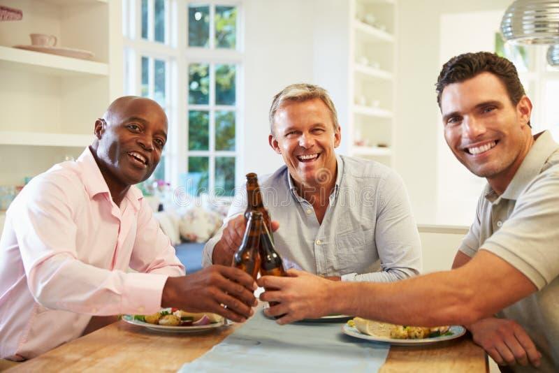 Reife männliche Freunde Sit At Table Drinking Beer und Essen lizenzfreie stockbilder