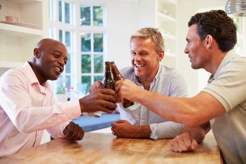 Reife männliche Freunde Sit At Table Drinking Beer und Unterhaltung stockfotografie