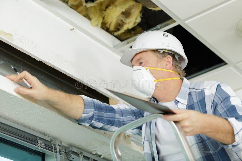 Reife Mannarbeitskraft, die in Dachboden klettert, um Hausdach zu isolieren lizenzfreies stockbild
