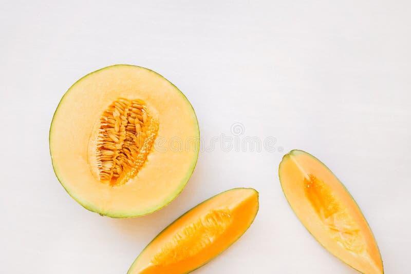 Reife Melonenhälfte und -scheiben lizenzfreie stockfotografie