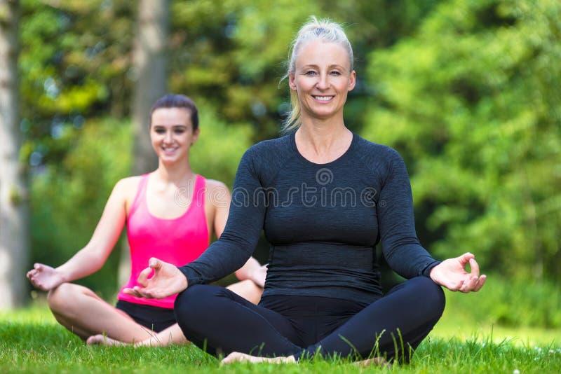 Reife Mitte-gealterte und junge Frauen-übendes Yoga draußen stockbild