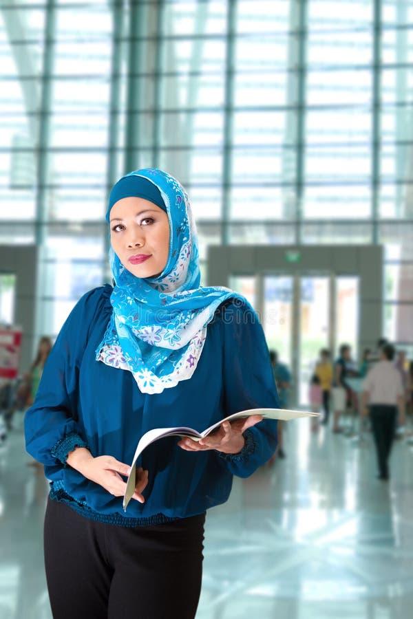 Reife moslemische Frau mit einem Buch in der Ausstellungshalle stockfotografie
