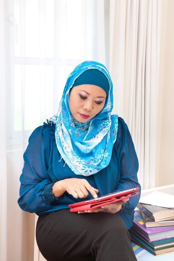 Reife moslemische Frau mit einem Buch in der Ausstellungshalle lizenzfreie stockfotografie