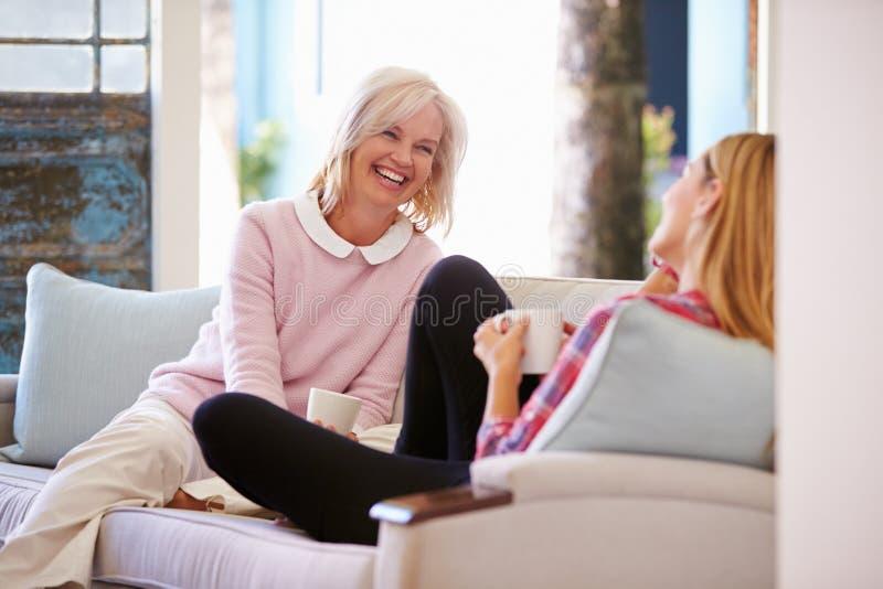 Reife Mutter mit der erwachsenen Tochter, die auf Sofa At Home sich entspannt stockfotos