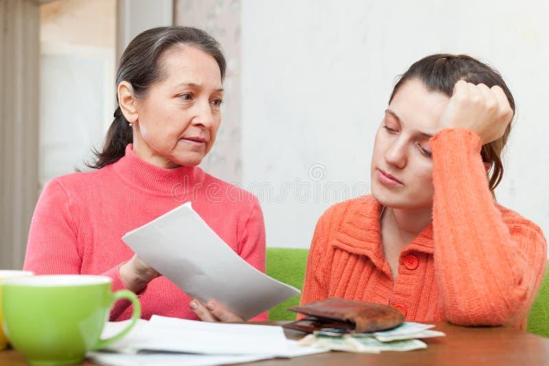 Reife Mutter schilt Tochter für Rechnungen oder Kredite stockfoto