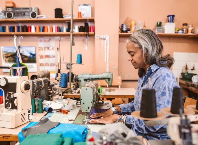 Reife Näherin, die in ihrer nähenden Werkstatt arbeitet stockfotos