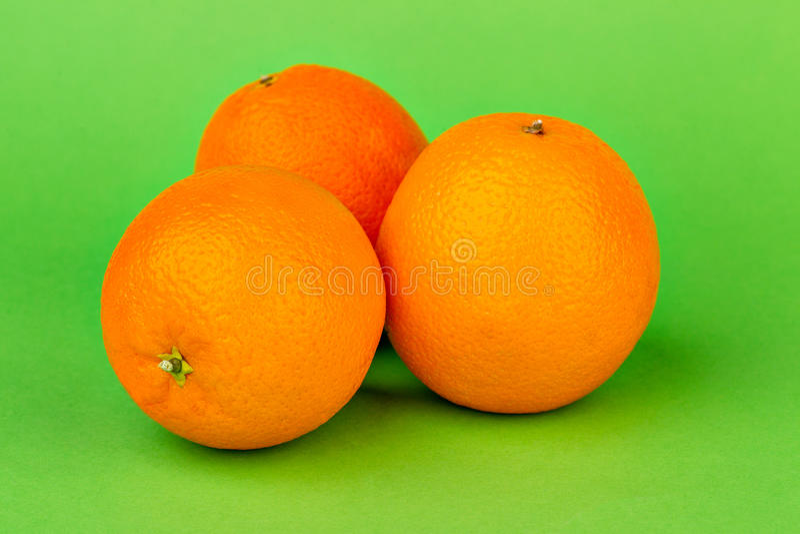 Reife Orangen auf einem grünen Hintergrund lizenzfreie stockfotografie