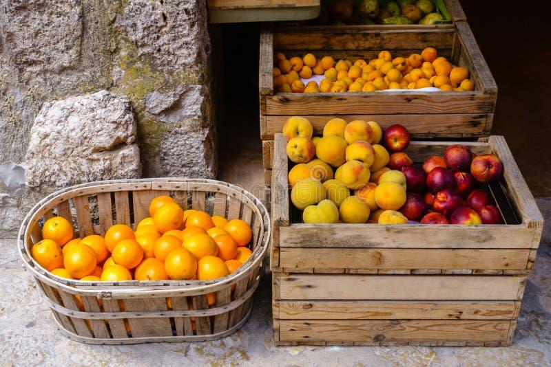 Reife Orangen, Pfirsiche, Nektarinen und Pflaumen in den Holzkisten für Verkauf stockbilder