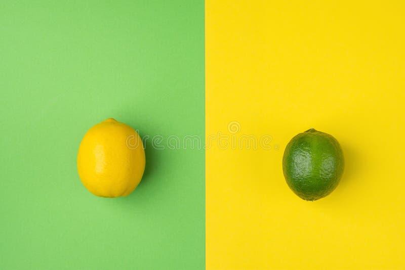 Reife organische Zitrone und Kalk auf grünem gelbem Hintergrund Spalte Duotone Angeredetes kreatives Bild Zitrusfrucht-Vitamine lizenzfreies stockbild