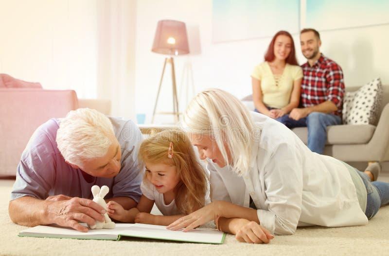 Reife Paarausgabenzeit mit ihrer Enkelin Glückliche Familie lizenzfreie stockfotografie