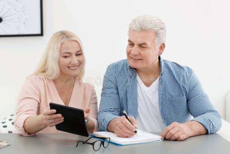 Reife Paare, die über Pensionszahlung denken lizenzfreie stockbilder