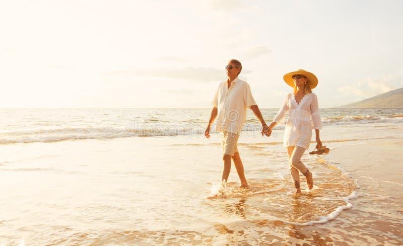 Reife Paare, die auf den Strand bei Sonnenuntergang gehen lizenzfreie stockfotos