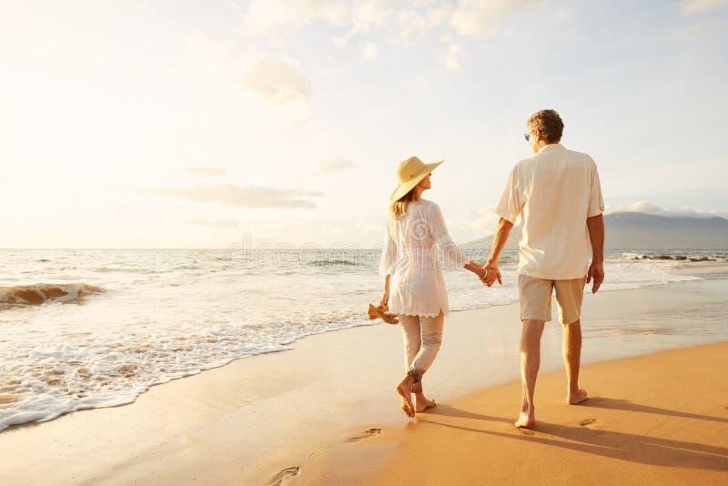 Reife Paare, die auf den Strand bei Sonnenuntergang gehen stockbild