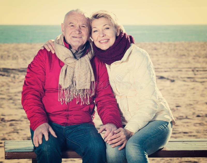 Reife Paare, die durch Meer sitzen lizenzfreies stockfoto