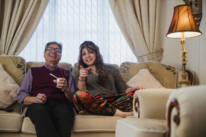 Reife Paare, die Fernsehkomödie aufpassen lizenzfreie stockfotos