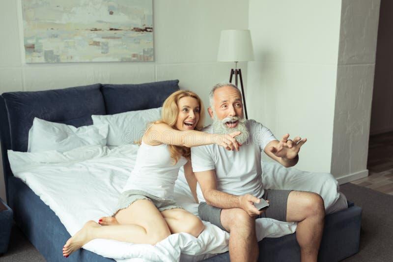 Reife Paare, die im Fernsehen beim auf Bett zu Hause sitzen lachen und zeigen lizenzfreies stockbild
