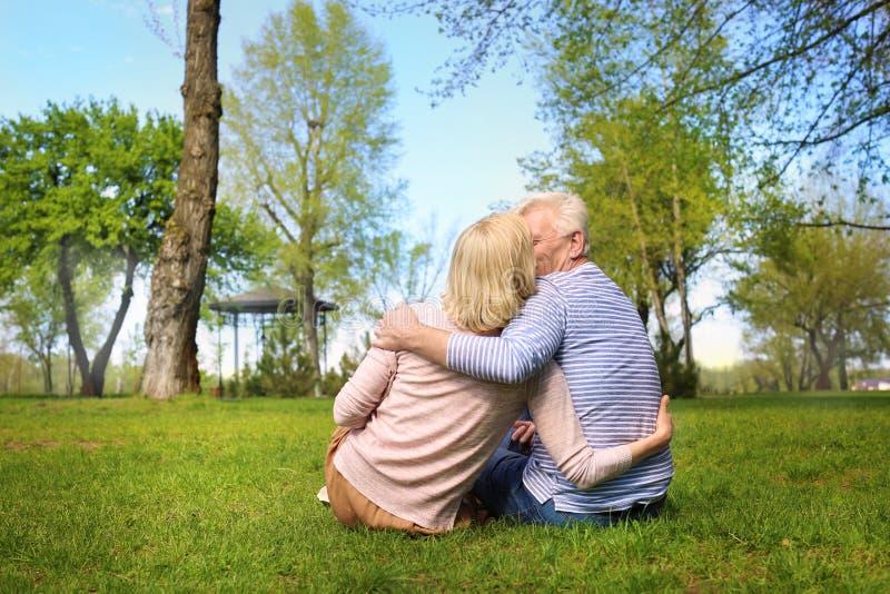 Reife Paare, die im Park am Frühlingstag stillstehen lizenzfreie stockfotos