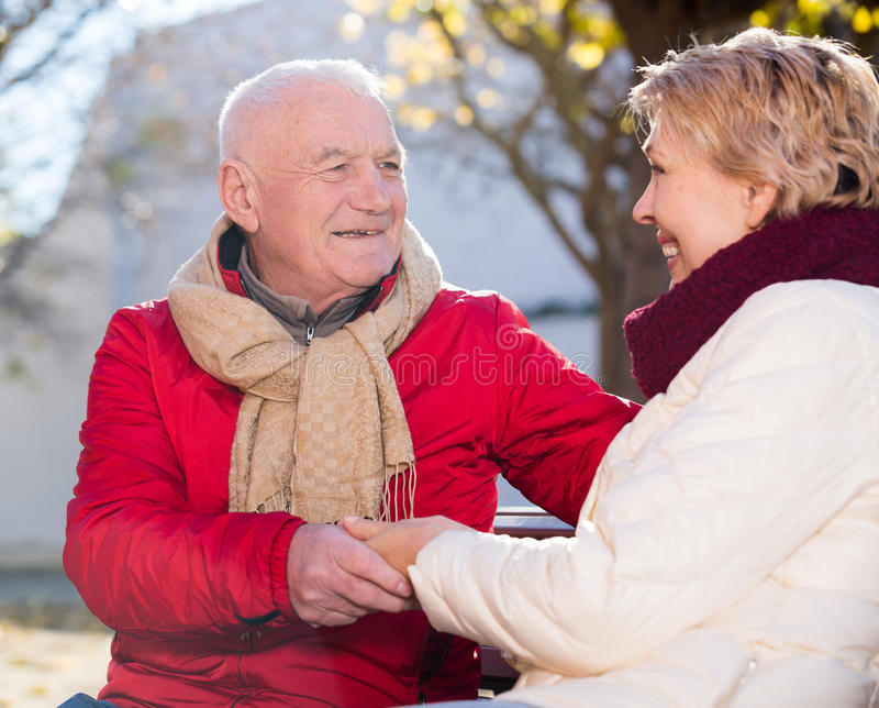 Reife Paare, die im Park sprechen lizenzfreie stockfotos