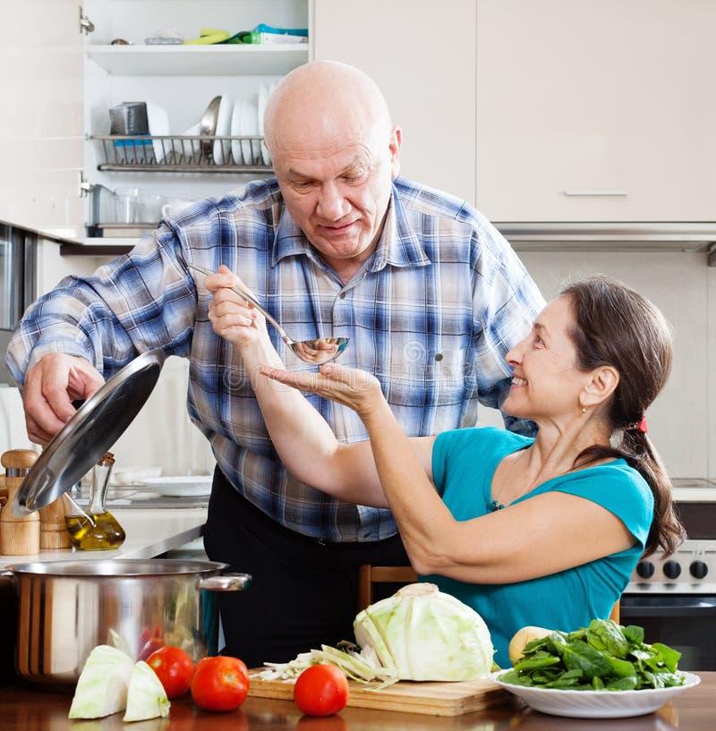 Reife Paare, die Lebensmittel mit Gemüse kochen stockbilder