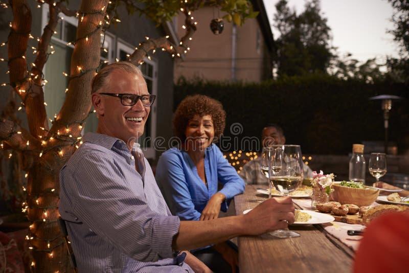 Reife Paare, die Mahlzeit im Freien im Hinterhof genießen stockfoto
