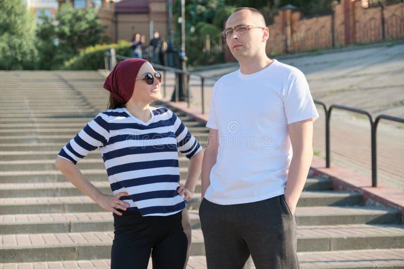 Reife Paare, die nahe der Treppe, dem l?chelnden gl?cklichen Mann und der Frau sprechen stockbild