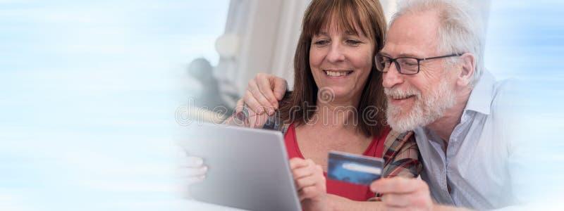 Reife Paare, die online mit Tablette und Kreditkarte kaufen lizenzfreie stockfotos