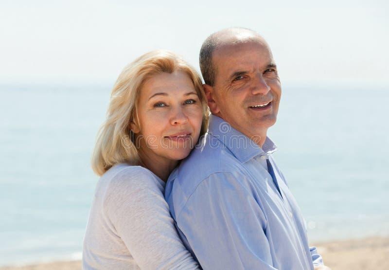 Reife Paare gegen Meer im Hintergrund lizenzfreie stockbilder