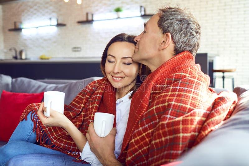 Reife Paare mit Bechern Kaffee unter einer Wolldecke im Raum lizenzfreies stockfoto