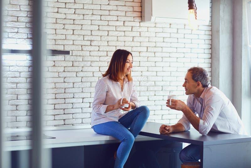 Reife Paare mit Tasse Kaffee zuhause lizenzfreie stockfotografie