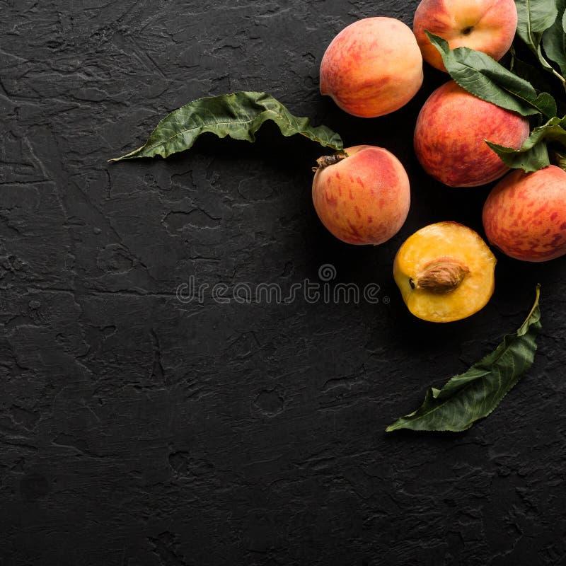 Reife Pfirsiche auf schwarzem Steinhintergrund Gesundes Lebensmittelkonzept, Draufsicht lizenzfreie stockbilder