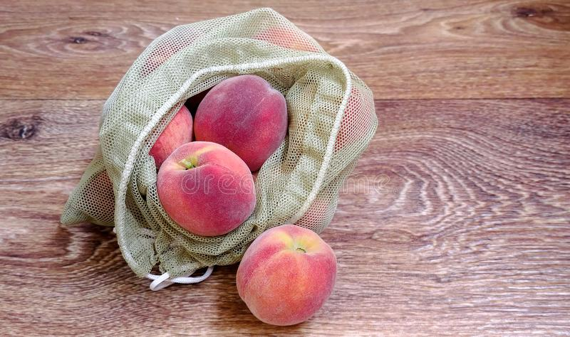 Reife Pfirsiche in wiederverwendbaren eco Taschen stockfotos