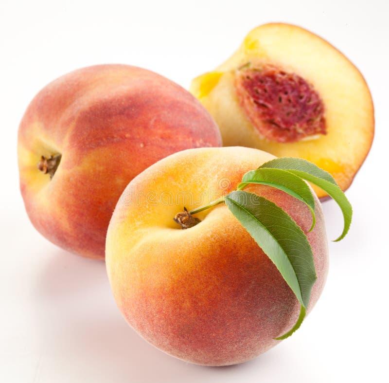 Reife Pfirsichfrucht mit Blättern und slises lizenzfreie stockfotos