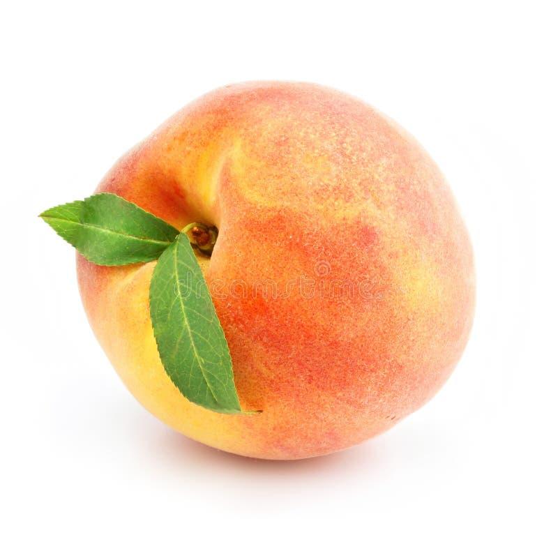 Reife Pfirsichfrucht mit den grünen Blättern getrennt lizenzfreie stockfotos