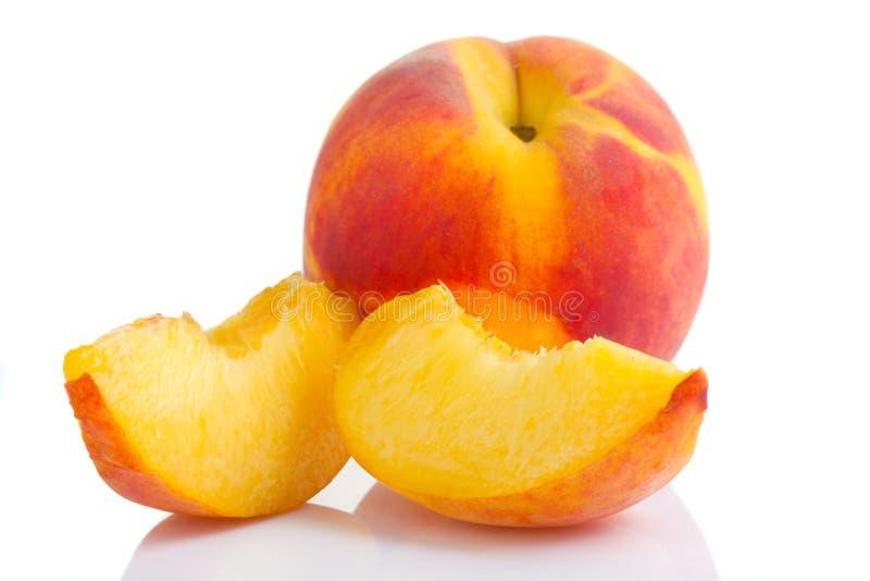 Reife Pfirsichfrucht mit Scheiben auf Weiß stockfotos